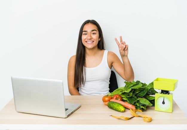 Młody dietetyk azjatycka kobieta na białym tle na białej ścianie pokazując znak zwycięstwa i szeroko uśmiechając się.