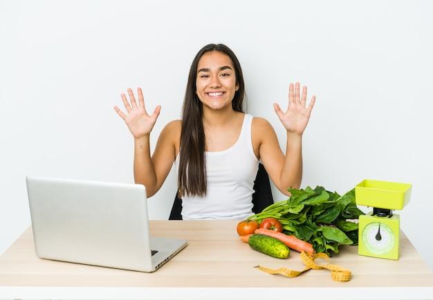 Młody dietetyk azjatycka kobieta na białym tle na białej ścianie pokazuje numer dziesięć rękami.