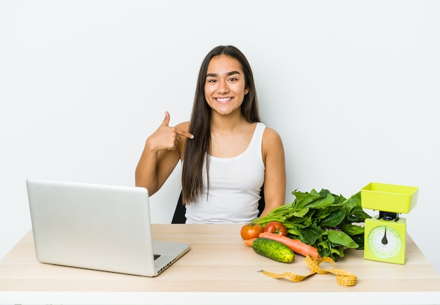 Młody dietetyk azjatycka kobieta na białym tle osoba, wskazując ręką na przestrzeni kopii koszuli, dumny i pewny siebie.