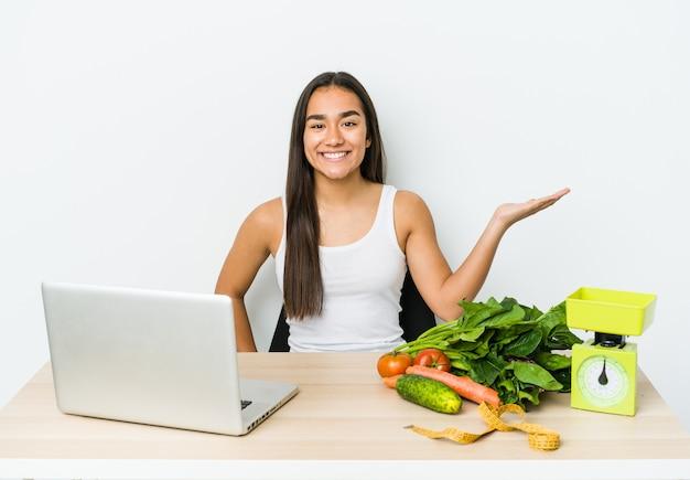 Młody dietetyk azjatycka kobieta na białym tle pokazując miejsce na dłoni i trzymając drugą rękę na talii.