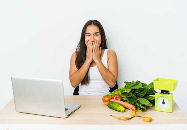 Młody dietetyk azjatycka kobieta na białym tle śmiejąc się z czegoś, obejmując usta rękami.