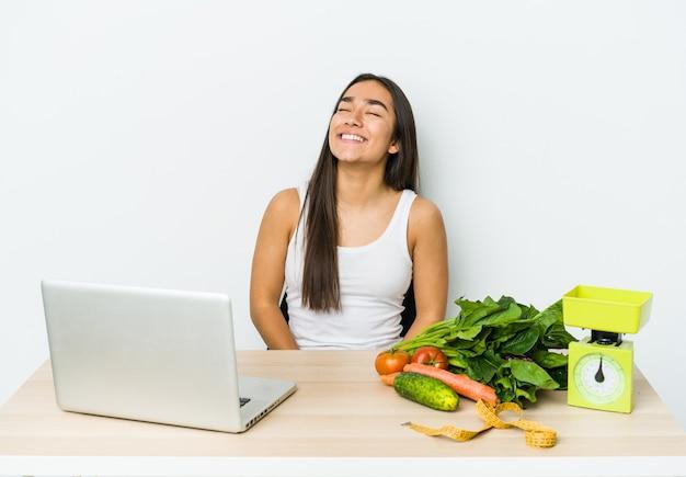 Młody dietetyk azjatycka kobieta na białym tle zrelaksowany i szczęśliwy śmiejąc się, wyciągnięty szyję pokazując zęby.
