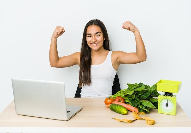 Młody dietetyk azjatykcia kobieta na białym tle pokazując gest siły z rękami, symbol kobiecej mocy