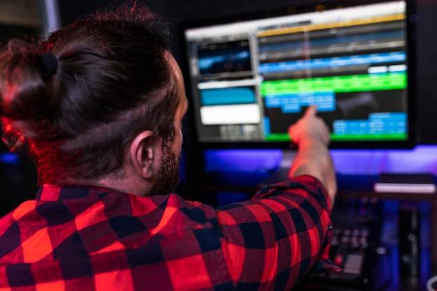 Młody dj pokazuje na komputerze w programie nagrywającym, jaki pomysł chce dodać do swojej nowej piosenki.