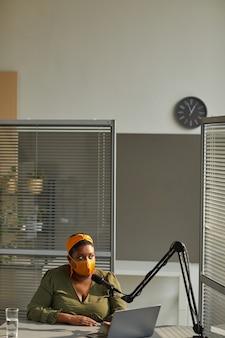 Młody dj radiowy w masce ochronnej siedzi przy stole z laptopem i mówi do mikrofonu