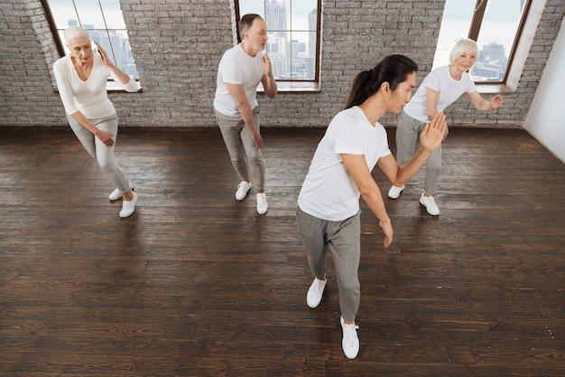 Młody długowłosy instruktor ubrany w białą koszulkę, odwracając się i trzymając zgięte ramiona, pokazując ćwiczenia swojemu gościowi