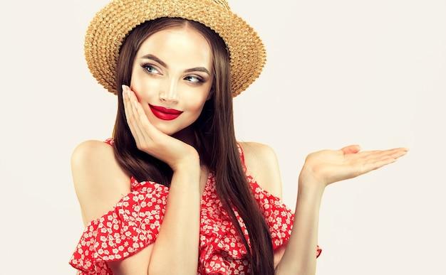 Młody, długowłosy model o figlarnym wyglądzie i ładnym uśmiechu na czerwonych ustach pokazuje produkt pod ręką z miejscem na kopię