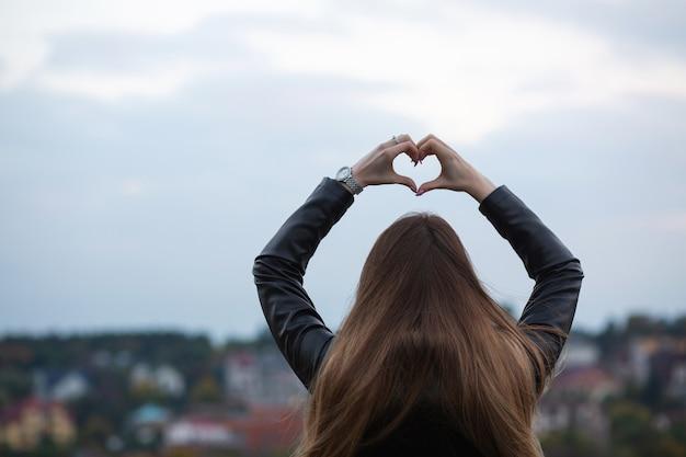 Młody długowłosy model przedstawiający symbol serca dwiema rękami na tle miasta. miejsce na tekst