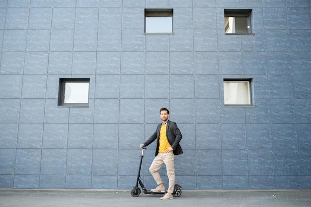 Młody, dobrze ubrany biznesmen w eleganckiej odzieży casual, stojącej przy ścianie nowoczesnego budynku podczas jazdy skuterem