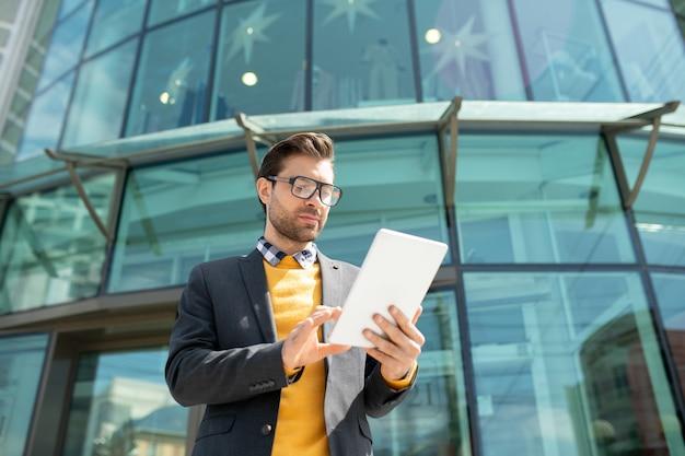 Młody, dobrze ubrany pracownik mobilny, przewijający w touchpadzie podczas wyszukiwania danych online na zewnątrz