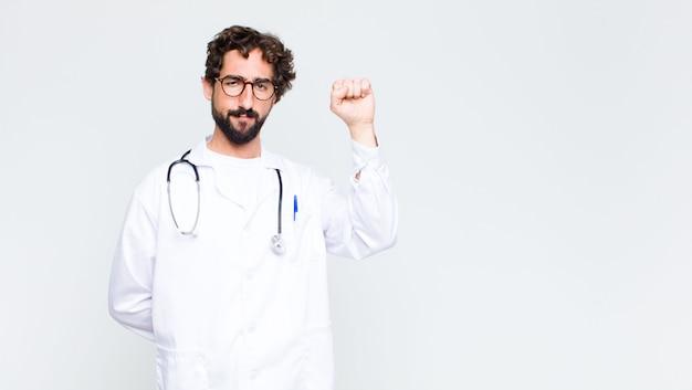 Młody doktor człowiek czuje się poważny, silny i zbuntowany, podnosząc pięść do góry, protestując lub walcząc o rewolucję przeciwko ścianie przestrzeni kopii