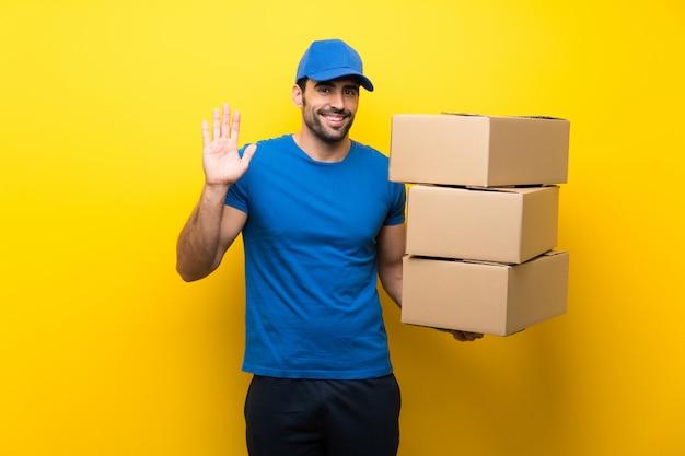 Młody doręczeniowy mężczyzna nad odosobnioną kolor żółty ścianą salutuje z ręką z szczęśliwym wyrażeniem