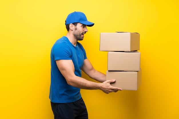 Młody doręczeniowy mężczyzna nad odosobnioną kolor żółty ścianą