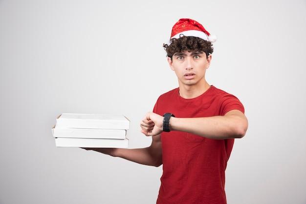 Młody doręczyciel sprawdza czas z pudełkami po pizzy.