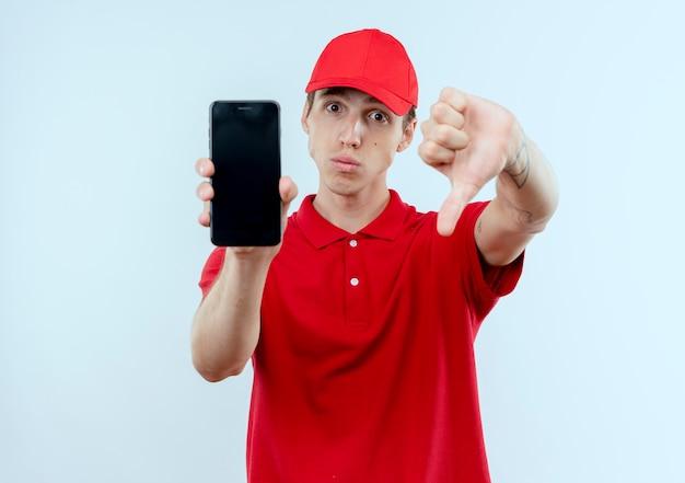Młody doręczyciel w czerwonym mundurze i czapce pokazuje niezadowolony smartfon patrząc do przodu, pokazując kciuki w dół stojącego nad białą ścianą