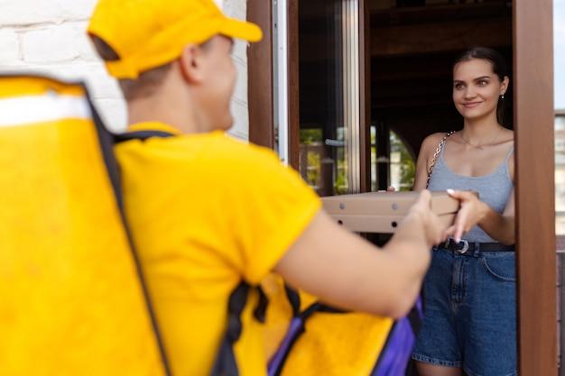 Młody doręczyciel w żółtym mundurze dostarcza klientom ideę wygody szybkości i komfortu