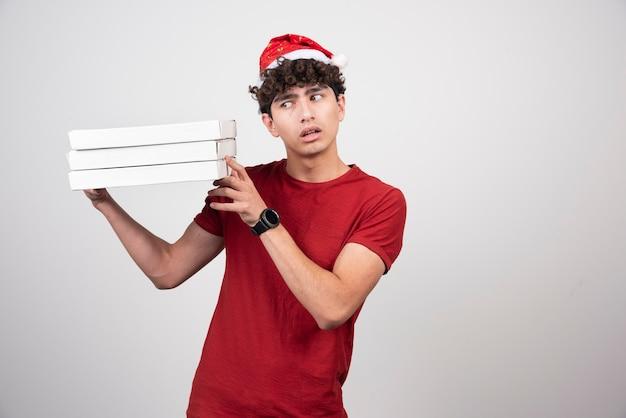 Młody doręczyciel ze stojącymi pudełkami po pizzy