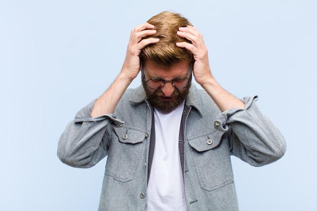 Młody dorosły blondyn czuje się zestresowany i sfrustrowany, podnosząc ręce do głowy, czując się zmęczony, nieszczęśliwy i z migreną