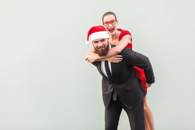 Młody dorosły brodaty mężczyzna krzywiąc się w aparacie. piegowata urocza brunetka przytula mężczyznę i piggyback. szare tło, zdjęcie studyjne