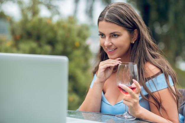 Młody dorosły długowłosy uśmiechnięta kobieta z kieliszek do wina na czacie online przed laptopem w godzinach popołudniowych na zewnątrz