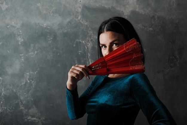 Młody dorosły hiszpański kobieta taniec flamenco na szarym tle