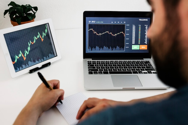 Młody dorosły inwestor studiujący rynek finansowy z wykresami na laptopie