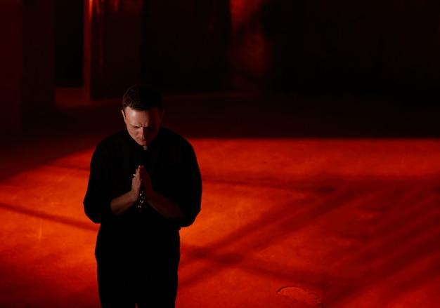 Młody dorosły kaukaski ksiądz katolicki na ciemnym czerwonym tle