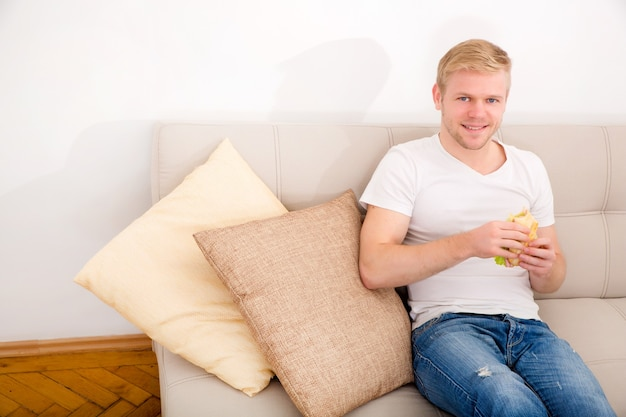 Młody dorosły mężczyzna je kanapkę w domu na kanapie.