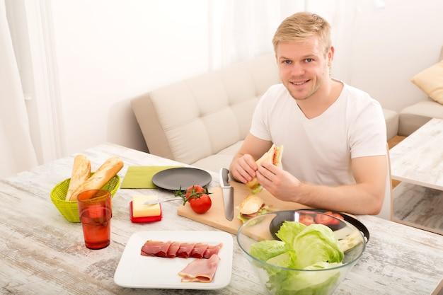 Młody dorosły mężczyzna je kanapkę w domu.