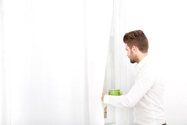Młody dorosły mężczyzna pije kawę w domu.