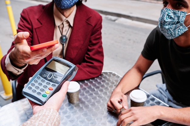 Młody dorosły mężczyzna płacący telefonem komórkowym za pomocą datafonu i ochronnej maski ochronnej - nowa norma
