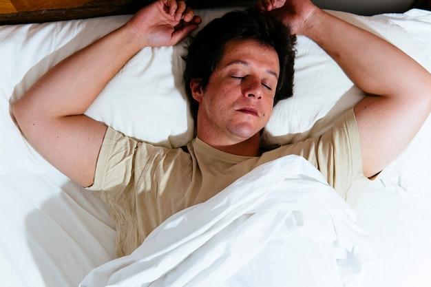 Młody dorosły mężczyzna śpi rano w łóżku