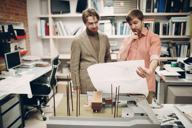 Młody dorosły myśli architekt pracujący przy stole z planem rysunków projektu i układem budynku w biurze architektonicznym