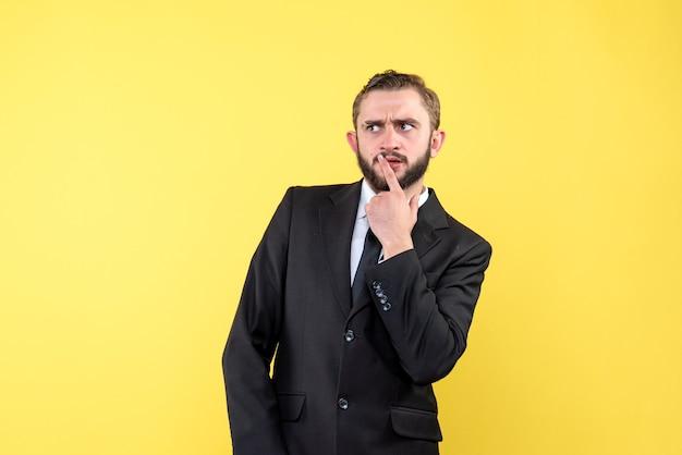 Młody dorosły myśli o wysokiej rozdzielczości z jego garnitur na żółto