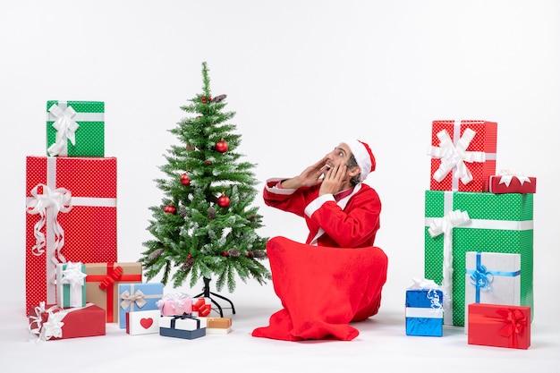 Młody dorosły przebrany za świętego mikołaja z prezentami i udekorowaną choinką siedzi w ziemi i mówi do kogoś z zaskoczenia