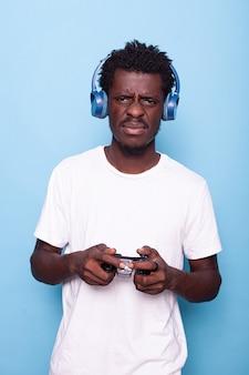 Młody dorosły przegrywający w grach wideo z kontrolerem