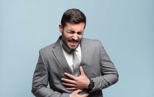 Młody dorosły przystojny biznesmen czuje się niespokojny, chory, chory i nieszczęśliwy, cierpi na bolesny ból brzucha lub grypę