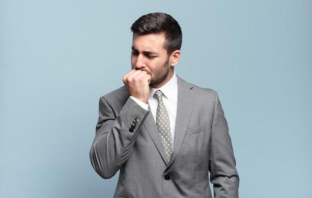 Młody dorosły przystojny biznesmen czuje się poważny, zamyślony i zatroskany, wpatrując się w bok z ręką przyciśniętą do brody