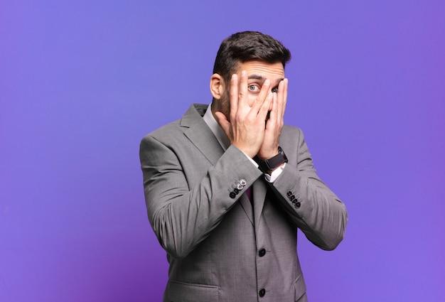 Młody dorosły przystojny biznesmen czuje się przestraszony lub zawstydzony, zerka lub szpieguje z oczami na wpół zakrytymi rękami
