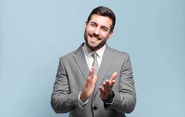 Młody dorosły przystojny biznesmen czuje się szczęśliwy i odnosi sukcesy, uśmiecha się i klaszcze w dłonie, mówiąc gratulacje z aplauzem