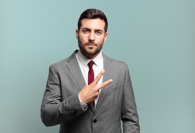 Młody dorosły przystojny biznesmen czuje się szczęśliwy, pozytywny i odnoszący sukcesy, z ręką tworzącą kształt litery v nad klatką piersiową, pokazując zwycięstwo lub pokój