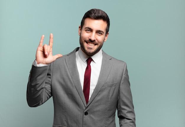 Młody dorosły przystojny biznesmen czuje się szczęśliwy, zabawny, pewny siebie, pozytywny i buntowniczy