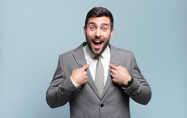Młody dorosły przystojny biznesmen czuje się szczęśliwy, zaskoczony i dumny, wskazując na siebie z podekscytowanym, zdziwionym spojrzeniem