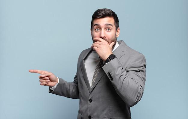 Młody dorosły przystojny biznesmen czuje się szczęśliwy, zszokowany i zaskoczony, zakrywa usta dłonią i wskazuje na boczną przestrzeń kopii copy
