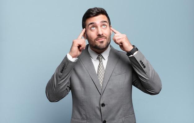 Młody dorosły przystojny biznesmen czuje się zdezorientowany lub wątpi, koncentruje się na pomyśle, intensywnie myśli, chce skopiować przestrzeń z boku