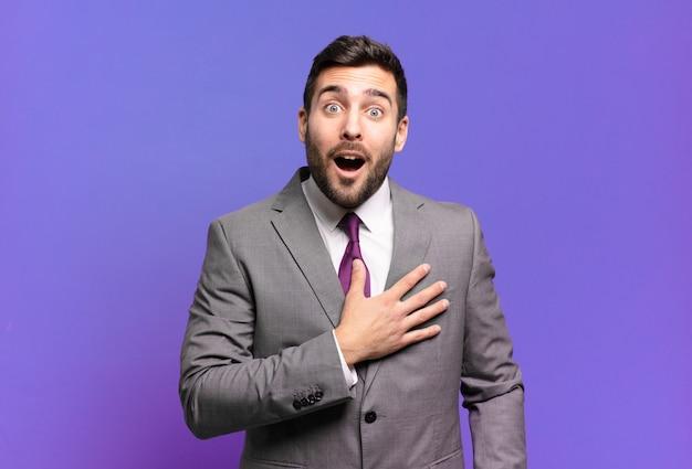 Młody dorosły przystojny biznesmen czuje się zszokowany i zaskoczony, uśmiecha się, bierze rękę do serca, jest szczęśliwy, że jest tym jedynym lub okazuje wdzięczność