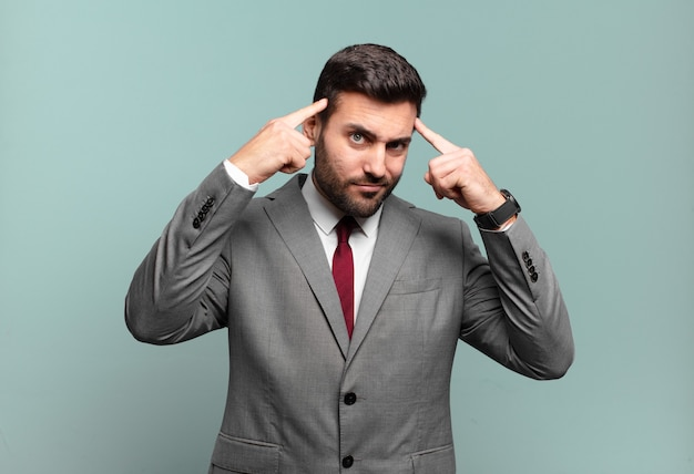 Młody dorosły przystojny biznesmen o poważnym i skoncentrowanym spojrzeniu, burzy mózgów i myśleniu o trudnym problemie