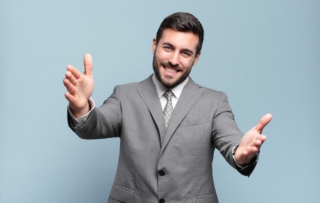 Młody dorosły przystojny biznesmen uśmiecha się radośnie, dając ciepły, przyjazny, kochający uścisk powitalny, czując się szczęśliwy i uroczy