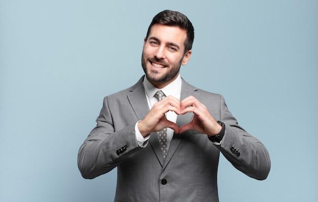 Młody dorosły przystojny biznesmen, uśmiechając się i czując się szczęśliwy, uroczy, romantyczny i zakochany, co kształt serca obiema rękami