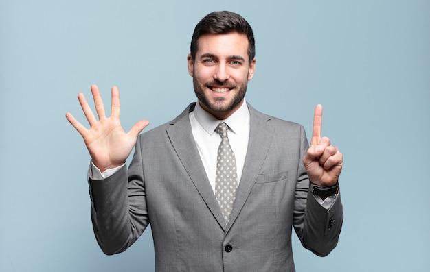 Młody dorosły przystojny biznesmen uśmiechnięty i wyglądający przyjaźnie, pokazując numer sześć lub szósty z ręką do przodu, odliczając w dół